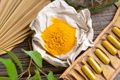 foto of curcuma  - Natural herbal tumeric capsules with fresh herb leaves and dry curcumin in paper - JPG