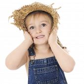 Close--up of an amazed preschooler tightly squeezing her ragged straw hat around her face.  On a whi