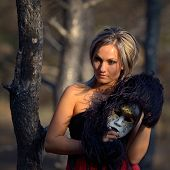 beautiful woman holding carnival mask