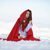 picture of cloak  - beautiful woman with red cloak sitting on the snow in winter - JPG