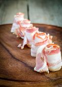 image of bacon strips  - Rolled Bacon Strips On Wooden Board Close Up - JPG