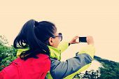 stock photo of emei  - woman hiker taking photo with cell phone at peak of emei mountain - JPG
