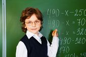 picture of clever  - Clever boy holds chalk near blackboard with mathematics equation in school - JPG