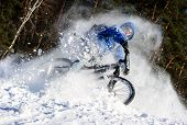 stock photo of snow forest  - Bicyclist riding on a mountain bike in the snow in the winter forest - JPG