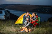 stock photo of camper  - Romantic evening. Charming couple near a fire while camping drinking wine