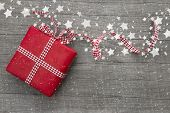 stock photo of gift wrapped  - Christmas Present wrapped in red paper on a wooden background for a voucher coupon  - JPG