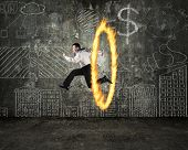 stock photo of juggler  - Man jumping through fire hoop with doodles wall background - JPG