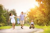 pic of children walking  - Happy young family having fun outside on the street of a village