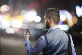 picture of boys night out  - Handsome young hipster with his smartphone outside in the night city - JPG