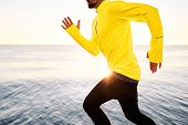 picture of blue  - Sport fitness runner running outside at sunset at beach near deep blue sea - JPG