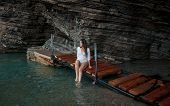 stock photo of cave woman  - Sexy young woman in white shirt sitting in sea cave - JPG