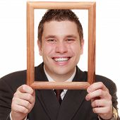 stock photo of dork  - Happy funny business man guy framing his face with wooden empty picture frame isolated on white background - JPG