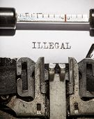 image of illegal  - Typewriter with white paper page on wooden table - JPG