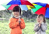 stock photo of rain  - two brothers play in rain outdoors - JPG