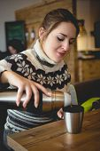 foto of thermos  - Portrait of beautiful woman in sweater pouring coffee from thermos in cup - JPG