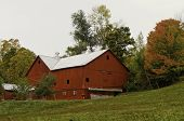 foto of barn house  - A view of a large red farm house on a hill - JPG