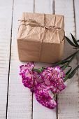 stock photo of carnation  - Carnations flowers and gift box on white wooden background - JPG