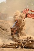 picture of track-hoe  - Track hoe excavator working on a top soil pile for later use on a new commercial construction development project - JPG