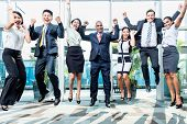 stock photo of indian  - Diversity business team jumping celebrating success - JPG