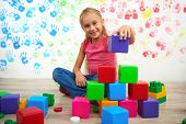 stock photo of human pyramid  - Little cute girl making pyramid of colored cubes and looking at the camera. Preschool center for children