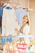 pic of pullovers  - Beautiful young woman choosing new pullover - JPG
