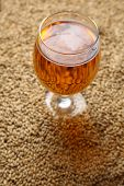 stock photo of malt  - Glass full of light beer standing on barley malt grains - JPG