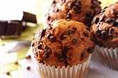 stock photo of chocolate muffin  - chocolate chip muffins on a table in the kitchen - JPG