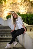 image of leggins  - girl in leggins and sneakers are sitting on the stairs in the evening