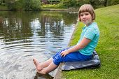 image of ponds  - Young caucasian girl sitting with bare feet in water of pond - JPG