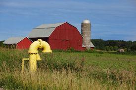 stock photo of gas-pipes  - Yellow Iron Gate Valves on the farm land - JPG