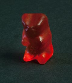 picture of gummy bear  - A gummy bear sitting on a black background - JPG