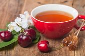 pic of black-cherry  - black english tea in red cup with cherry on wooden background - JPG