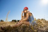picture of tallgrass  - Beautiful hippie looking girl sitting on a meadow - JPG