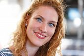 image of redhead  - Redhead woman with curly hair indoor portrait - JPG