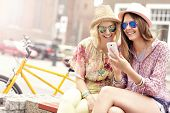 stock photo of tandem bicycle  - A picture of two girl friends using smartphone while riding tandem bicycle - JPG
