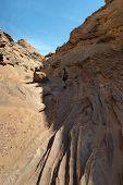 stock photo of cave woman  - Woman Hiker Backpacker hiking narrow slot canyon - JPG