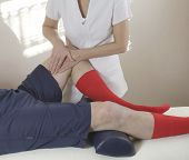 stock photo of thighs  - Female sports massage therapist working on male client - JPG