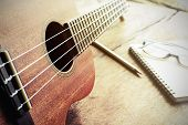 pic of ukulele  - Close up of ukulele on old wood background with soft light Vintage tone - JPG