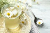 stock photo of chamomile  - Glass of cold chamomile tea with ice cubes and chamomile flowers on color wooden background - JPG