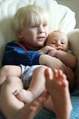 stock photo of big-foot  - A toddler aged big brother his hugging his little baby sister as the cuddle on the living room couch watching a movie - JPG