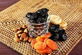 stock photo of prunes  - Prunes and other dried fruits on wicker mat - JPG