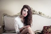 stock photo of mystique  - Pretty model girl wearing white dress sitting on victorian sofa posing for camera with captivating facial expression - JPG