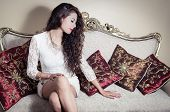 image of mystique  - Pretty model girl wearing white dress sitting on victorian sofa posing for camera with legs crossed looking down - JPG