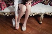pic of mystique  - leg caption of model girl wearing white dress sitting on victorian sofa with one shoe on left foot and holding other hand over right toes - JPG