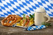 image of pretzels  - Fried Bavarian sausages on potato salad served with pretzels and half a liter of Bavarian beer in a tankard - JPG