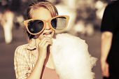 pic of candy cotton  - Happy teen girl eating cotton candy on a city street - JPG