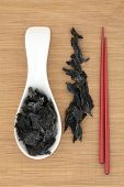 picture of edible  - Wakame edible seaweed with chopsticks over bamboo background - JPG
