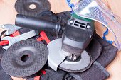 stock photo of friction  - Electric grinder along with spare grinding wheels on the working table - JPG