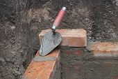 stock photo of trowel  - on the brick wall lies a trowel - JPG