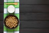 pic of cereal bowl  - Dried berry and oatmeal breakfast cereal in rustic bowl with a glass of milk photographed overhead on dark wood with natural light - JPG